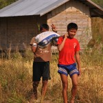 School boys carrying rice back to the village